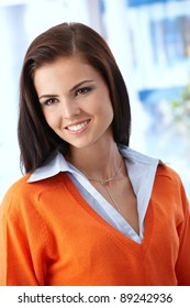 Beautiful woman smiling in orange pullover, looking away.?