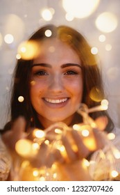 beautiful woman smiling, portrait with fairy lights glowing