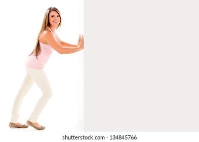 Beautiful woman smiling an pushing a wall