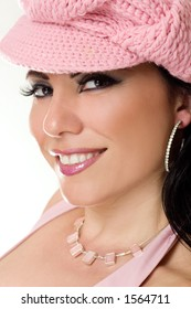 Beautiful woman smiling wearing pink hat jewelleryand glamorous makeup