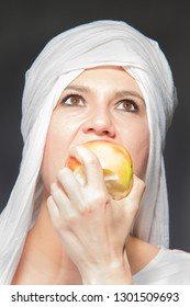 Beautiful woman smiling in white hijab licking forbidden friut apple