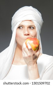 Beautiful woman smiling in white hijab eating an apple