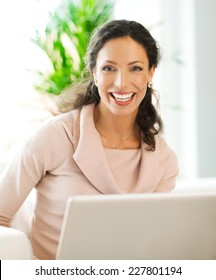 Beautiful woman smiling and working on laptop - close up.