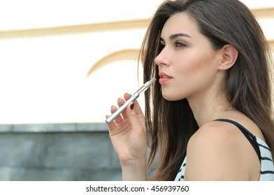 Beautiful woman smokes an electronic cigarette outdoors. She has perfect skin and wearing a striped t-shirt.