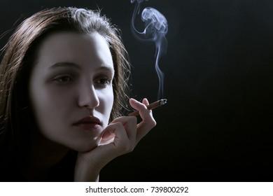 beautiful woman smoking cigarette on black background