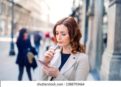 Beautiful woman smoking e-cigarette on the street.