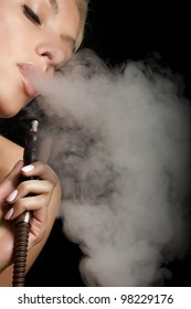 Beautiful woman smoking a hookah and smoke issues from the mouth