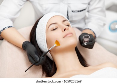Beautiful woman with smooth skin relaxing and enjoying spa procedures. Beautician applying anti-acne mask, making face peeling. Concept of facial, rejuvenation and regeneration of skin.