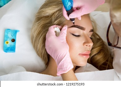 Beautiful woman with smooth, young skin, sitting in a beautician. A beautician performs modeling permanent eyebrows makings.Permanent makeup treatment.