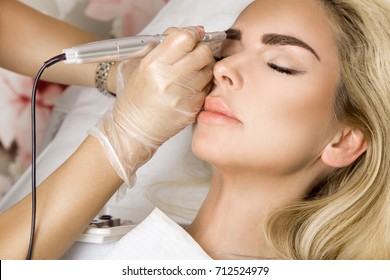 Beautiful woman with smooth, young skin, sitting in a beautician. A beautician performs modeling permanent eyebrows makings.
