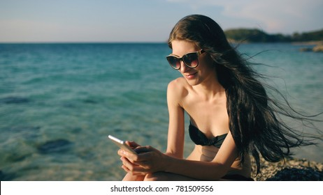 Beautiful woman sms texting using app on smart phone at beach sunset during vacation