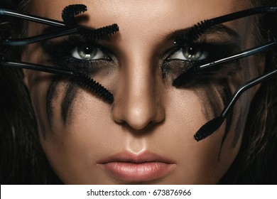 Beautiful woman with smudges of makeup on her face and broken mascara brushes