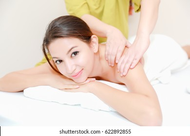 Beautiful woman in spa environment.Happy relaxed woman acupuncture patient receiving a therapy treatment on the back.Attractive young woman at the spa salon, picture of happy relaxed woman in spa.