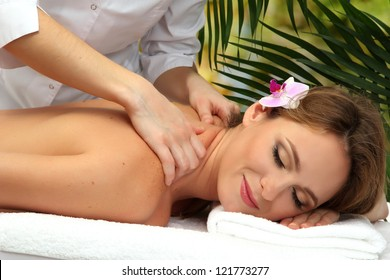 beautiful woman in spa salon  getting massage, on palm leaves background