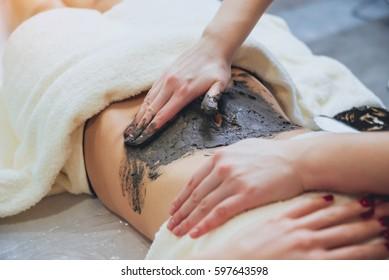Beautiful woman in spa salon getting mud body massage with scrub