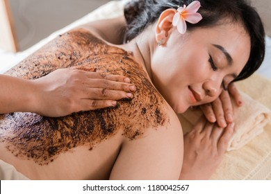 Beautiful woman in spa salon having spa therapy coffee scrub procedure with hands of masseur