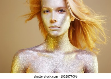 Beautiful Woman with Sparkles on her Face and body. Beauty Blonde Girl with Art Make-Up in Color Light. flying Hair Model with Colorful Makeup