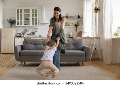 Beautiful woman spinning in circle hold hands little daughter standing in living room, nanny spend day with small girl at home, leisure activity active lifestyle, priceless time with offspring concept