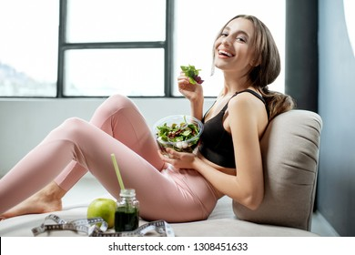 Beautiful woman in sportswear having a snack with healthy green food, resting on the couch after the training at home. Healthy lifestyle concept