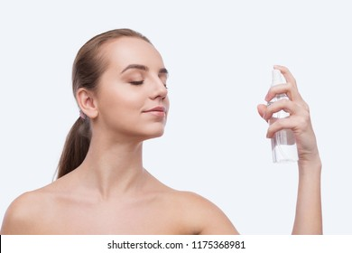 Beautiful woman spraying on face isolated on white background