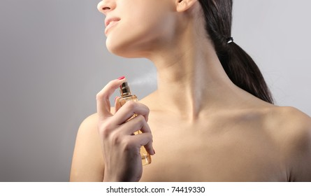 Beautiful woman spraying some perfume on her neck