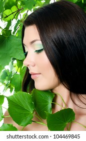 Beautiful woman with spring green leaves. Skincare