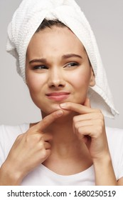 A beautiful woman squeezes acne on her face and a white towel