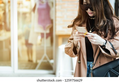 beautiful woman stand up front of store waite for shopping and use smartphone to communication