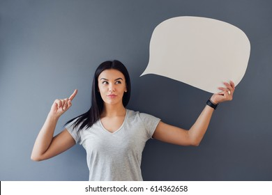 Beautiful woman standing against a grey background and holding a speech bubble