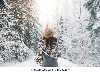 Beautiful woman standing among snowy trees in winter forest and enjoying first snow. Wearing hat, plaid scarf and coat. Wanderlust and boho style