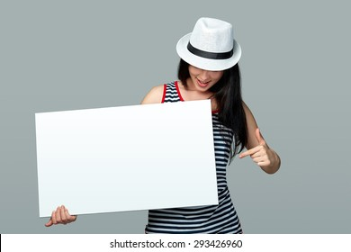 Beautiful woman standing behind, holding white blank advertising board banner in white summer  hat, on gray background