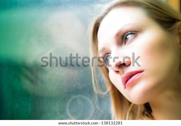 Beautiful woman standing by a window looking outside