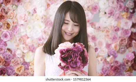 Beautiful woman standing in front of floral wall decoration