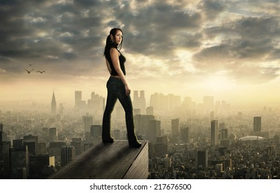 Beautiful woman is standing high above a big city