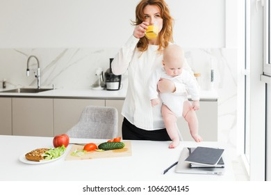 Beautiful woman standing and holding her cute little baby while drinking juice and cooking on kitchen isolated