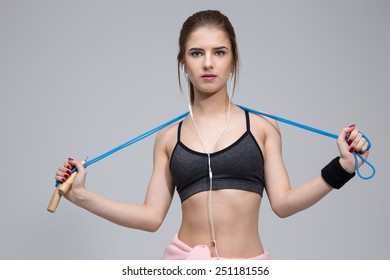 Beautiful woman standing with jumping rope over gray background
