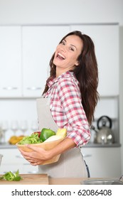 Beautiful woman standing in kitchen with apron
