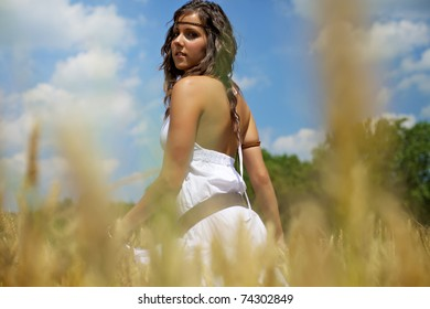 Beautiful woman standing in the middle of a golden wheat field on a hot summer afternoon. Color image with warm tones and a fresh feeling good for lifestyle and healthy themes.