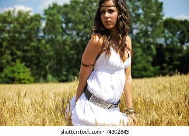 Beautiful woman standing in the middle of a wheat field on a hot summer afternoon. Color image photography with warm tones and a nice fresh feeling of happiness and serenity.