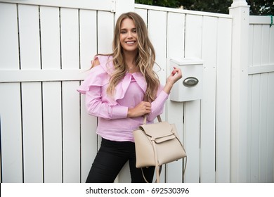 Beautiful woman standing near house fence and mail box wearing casual summer outfit.
