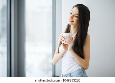 Beautiful woman standing near windows. Beautiful morning