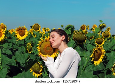 Beautiful  woman standing on a meadow with sunflowers and smiling happily