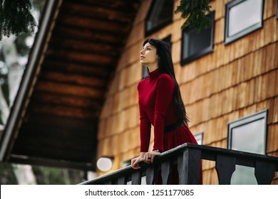 Beautiful woman standing on the porch of wooden house at forest and enjoy the view