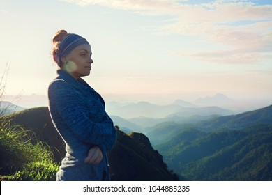 Beautiful woman is standing on top of a mountain