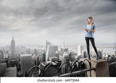 Beautiful woman standing on the top of a skyscraper and using a mobile phone