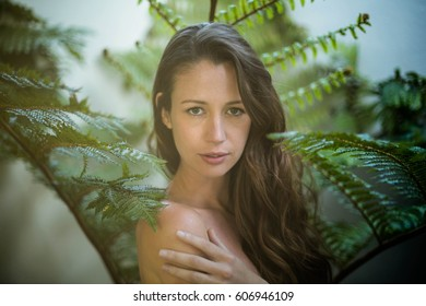 Beautiful woman standing outdoors against green plants