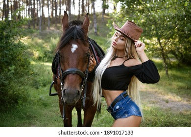 Beautiful woman stands with a horse in nature on the background of the forest
