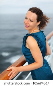 Beautiful woman stands on board of large ship and clings to railing