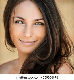 beautiful woman stands sideways dark hair bare shoulder smiling