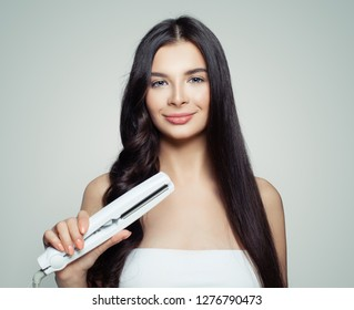 Beautiful woman with straight hair and curly hair using hair straightener. Cute girl straightening healthy hair with flat iron.